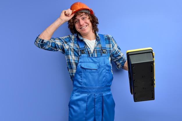 Verantwortlicher hart arbeitender fröhlicher ingenieur, der werkzeugkasten hält
