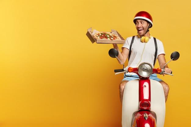 Verantwortlicher hübscher männlicher fahrer auf roller mit rotem helm, der pizza liefert