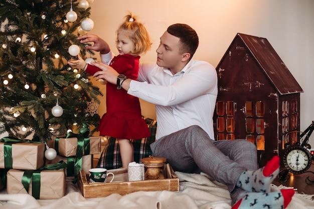 Verantwortlicher mann, der niedliches kind hilft, dekorationen auf weihnachtsbaum zu setzen