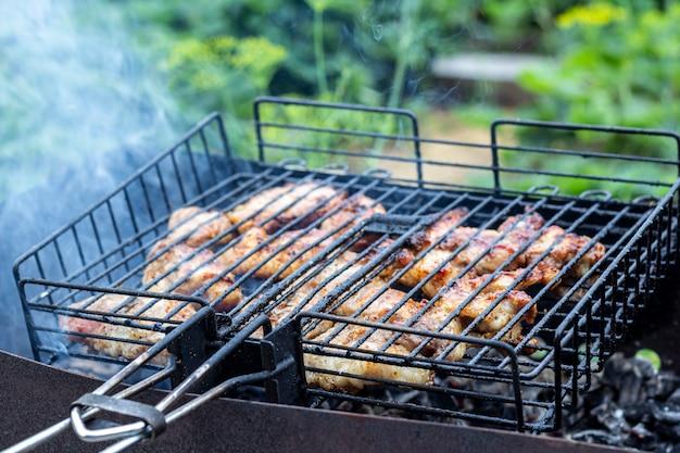 Verarbeiten sie das kochen von fleischigem steak auf einem grill im freien. picknick, essen im freien. metallgrill