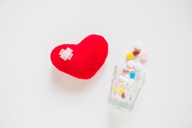 Verband auf dem roten herzen angefüllt mit vielen pillen, die vom glas auf weißem hintergrund überlaufen