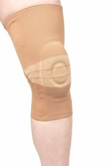 Verband zum befestigen des verletzten knies des menschlichen beins auf einem weißen hintergrund.