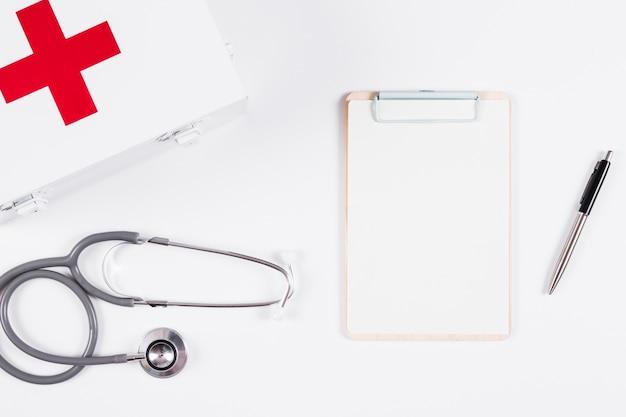 Verbandkasten; stethoskop und klemmbrett auf weißem hintergrund