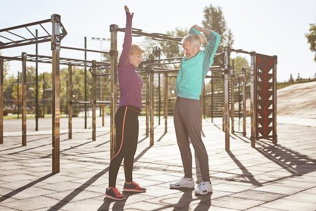 Verbesserung der gesundheit aktives und gesundes reifes familienpaar in sportbekleidung, das morgengymnastik macht