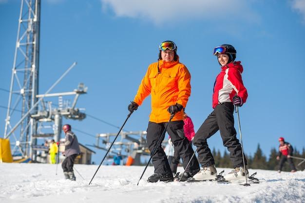 Verbinden sie das halten der skis, die zusammen auf bergspitze an einem winterurlaubsort mit skiliften und blauem himmel stehen
