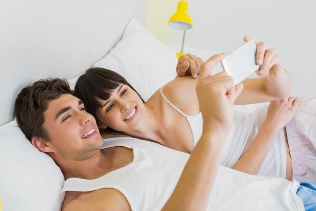 Verbinden sie das lügen auf bett und das betrachten des handys im schlafzimmer