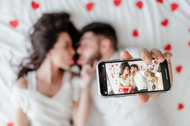 Verbinden sie den mann und frau, die zu hause selfie am telefon auf bett machen