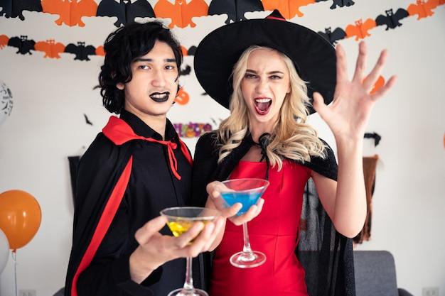 Verbinden sie jungen kaukasischen mann und frau in den vampiren und in hexenkleidung, die champagnerglas halten