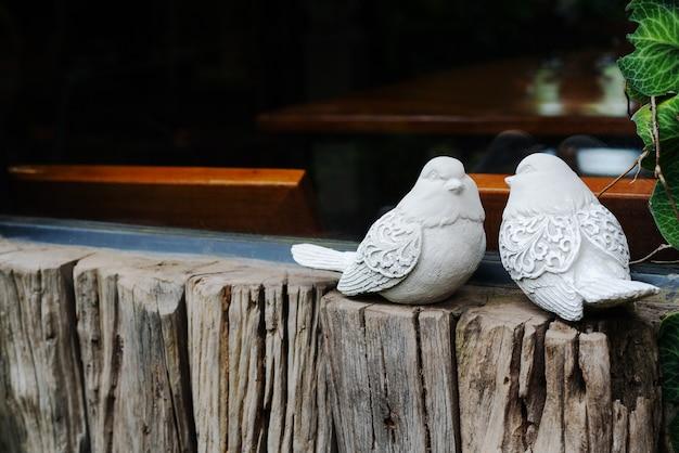 Verbinden sie vögel, zwei weiße vogelstatuen auf dem hölzernen nahen fenster