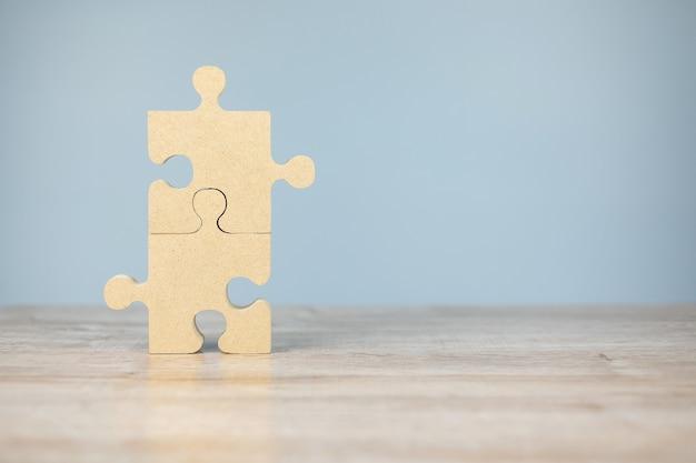Verbindungspaar puzzleteil, holzpuzzle auf tisch. geschäftslösungen, mission, erfolg, ziele und strategiekonzepte