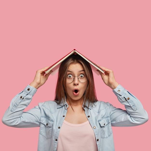 Verblüffte emotionale studentin hält buch auf dem kopf, ist schockiert, weil sie keine zeit für die prüfungsvorbereitung hat, wundert sich über den beginn des neuen studienjahres, gekleidet in jeanshemd, posiert drinnen. studienkonzept