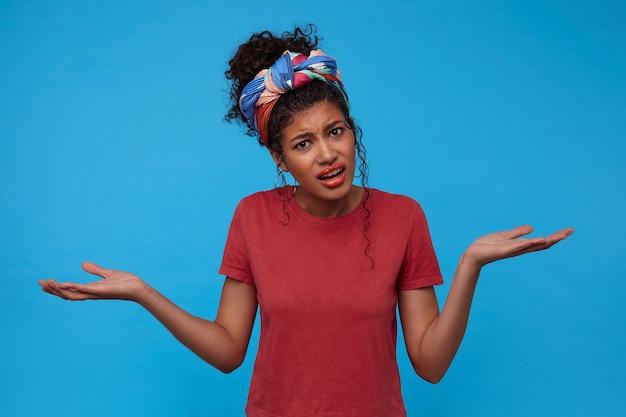 Verblüffte junge dunkelhaarige lockige frau in burgunderfarbenem t-shirt runzelte die stirn, während sie verwirrt mit erhobenen handflächen zuckte, isoliert über der blauen wand