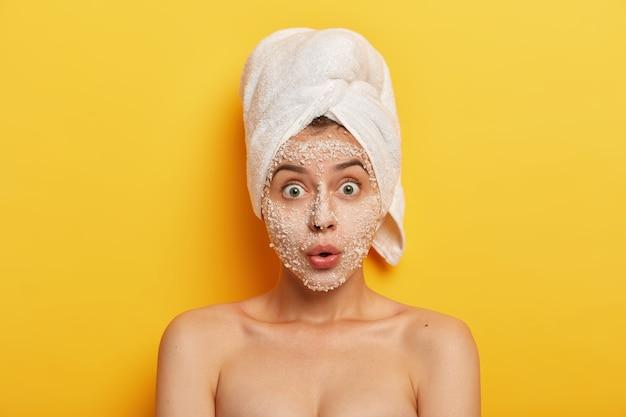 Verblüffte junge frau trägt natürliche meersalzmaske auf, reduziert aknen und pickel, starrt mit weit geöffneten augen, gesunde haut, kümmert sich um den teint, hat spa-therapie im badezimmer. hygiene und wellness