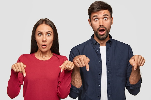 Verblüffte junge kolleginnen und kollegen zeigen mit beiden zeigefingern auf den boden, bemerken etwas unerwartetes und aufregendes, stehen schulter an schulter,