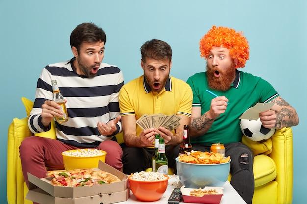 Verblüffte männer schauen überraschend auf bargeld, freuen sich darauf, eine wette zu gewinnen, schauen sich ein fußballspiel im fernsehen an, spielen und essen fast food. emotionaler typ mit viel geld, genieße die liga der champions