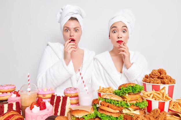 Verblüffte, vielfältige frauen hungern nach zucker- und fettreichen lebensmitteln und essen fast food