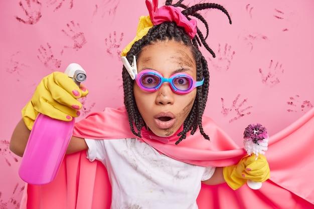 Verblüffte weibliche superheldin mit dreadlocks, die im haushalt beschäftigt sind, hält reinigungsmittel und schmutzige bürste, die beim waschen beschäftigt ist, hat einen lustigen look isoliert über rosa wand
