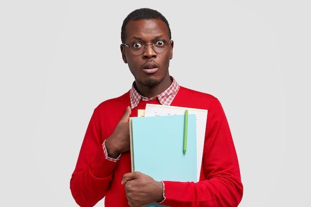 Verblüffter dunkelhäutiger gelehrter, der schockiert ist, unerwartete fragen zu stellen, hält lehrbücher und papiere mit stift