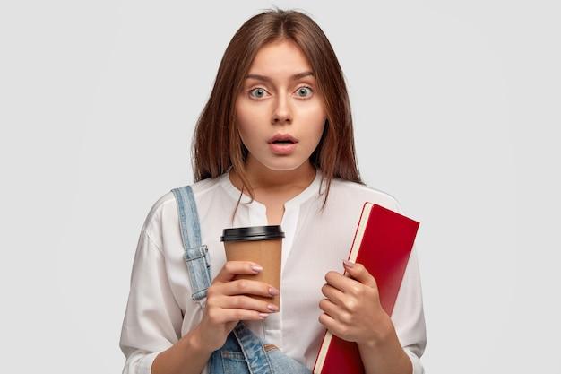 Verblüffter emotionaler college-student sieht mit verwirrtem ausdruck aus, hält kiefer vor staunen fallen