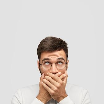 Verblüffter junger mann mit dunklem haar, bedeckt den mund mit handflächen, schaut nach oben, versucht leise zu sein und keinen ton zu erzeugen