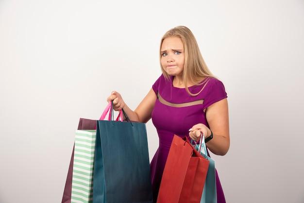 Verblüffter shopaholic, der bunte einkaufstaschen hält.