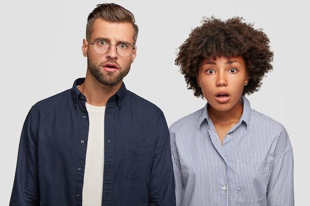 Verblüfftes familienpaar gemischter rassen reagiert auf plötzliche nachrichten