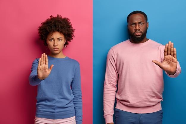 Verbots-symbol. ernsthafter unzufriedener schwarzer mann und frau machen stopp-geste mit handflächen, schauen unzufrieden, tragen freizeitkleidung