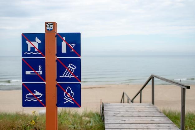 Verbotsschilder am strand gegen meer in der nähe von treppen
