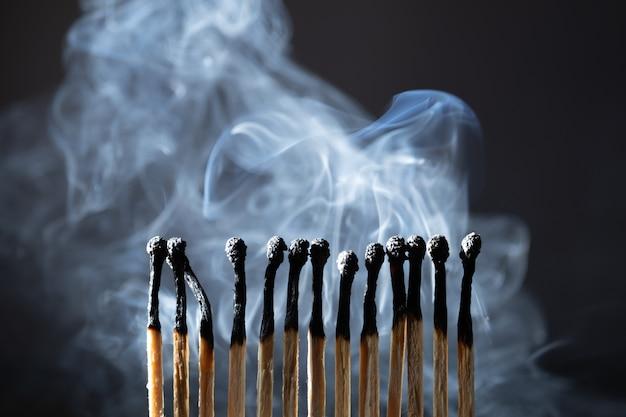 Verbrannte, ausgelöschte streichhölzer isoliert mit rauch auf schwarzem hintergrund