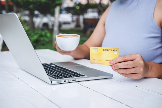 Verbraucher der jungen frau, der kreditkarte hält und auf laptop für das on-line-einkaufen und die zahlung schreibt, schließen einen kauf im internet, on-line-zahlung, vernetzung ab und kaufen produkttechnologie