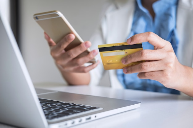 Verbraucher der jungen frau, der smartphone, kreditkarte hält und auf laptop für das on-line-einkaufen und die zahlung schreibt, schließen einen kauf im internet, eine on-line-zahlung, eine vernetzung ab und kaufen produkttechnologie