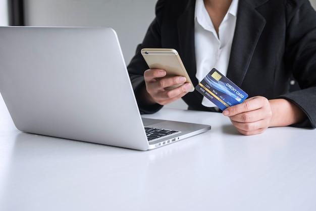 Verbraucher der jungen frau, der smartphone, kreditkarte hält und auf laptop für das on-line-einkaufen und die zahlung schreibt, schließen einen kauf im internet, online-zahlung, vernetzung ab und kaufen produkttechnologie