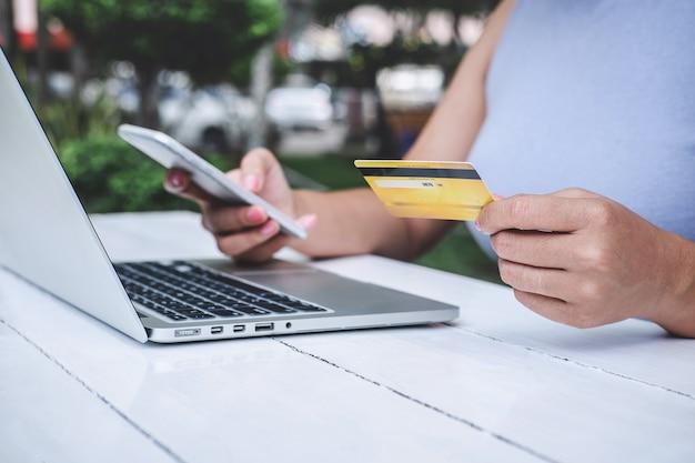 Verbraucher, der smartphone, kreditkarte hält und auf laptop für das on-line-einkaufen und die zahlung schreibt