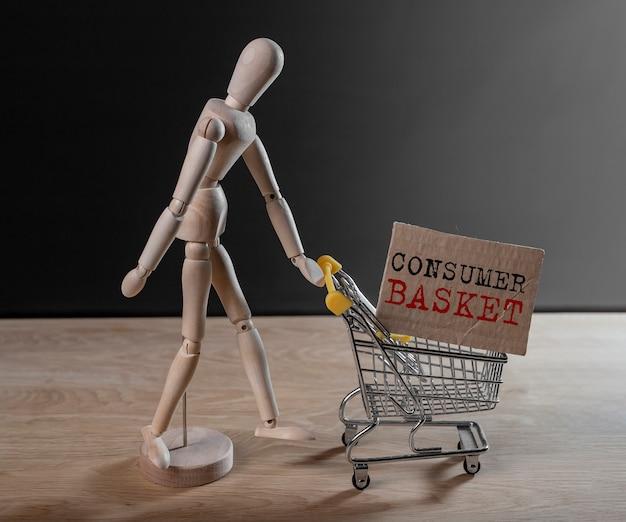 Verbraucherkorbtext im einkaufswagen, der von holzpuppe geschoben wird.