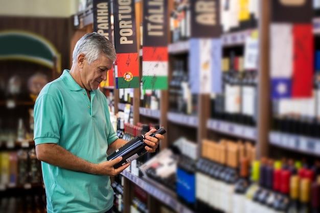 Verbrauchermann, der weine im supermarkt wählt. brasilianer.