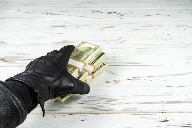 Verbrechen-konzept-mann in den schwarzen lederhandschuhen, die ziegelsteine des geldes halten