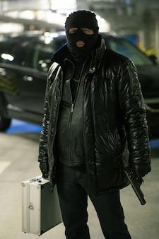 Verbrecher in schwarzer jacke und sturmhaube auf dem kopf, der pistole und koffer mit bargeld hält, während auf parkplatz stehen
