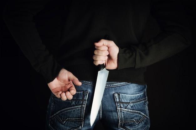 Verbrecher mit großem scharfem messer hinter seinem rücken