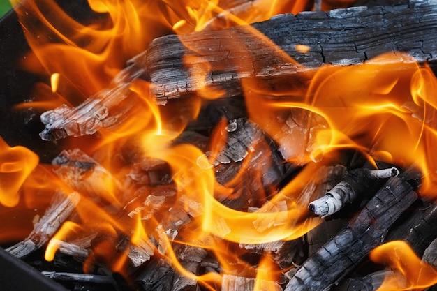 Verbrennung von holz in einer kohlenpfanne. feuer, flammen. grill oder bbq