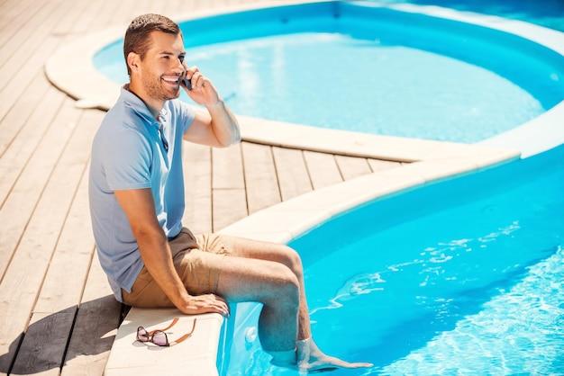 Verbringen sie tolle zeit am pool. schöner junger mann im poloshirt, der am pool sitzt und mit dem handy spricht