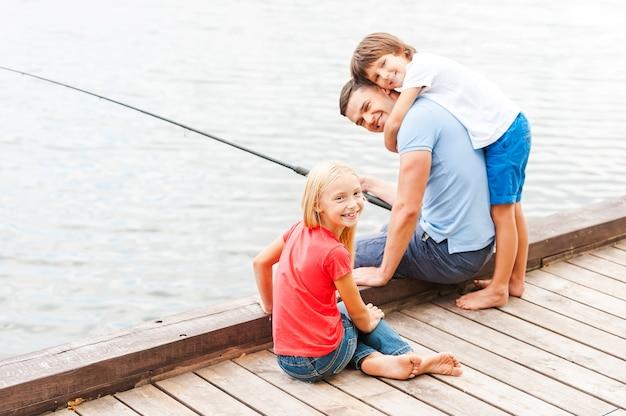Verbringen sie tolle zeit mit vater. glücklicher vater, der mit seinen kindern fischt, während er zusammen am flussufer sitzt