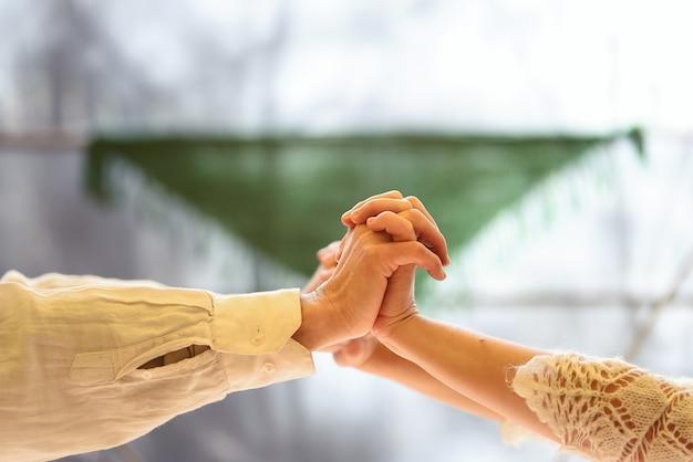 Verbundene und ineinander verschlungene hände eines weiß gekleideten paares.