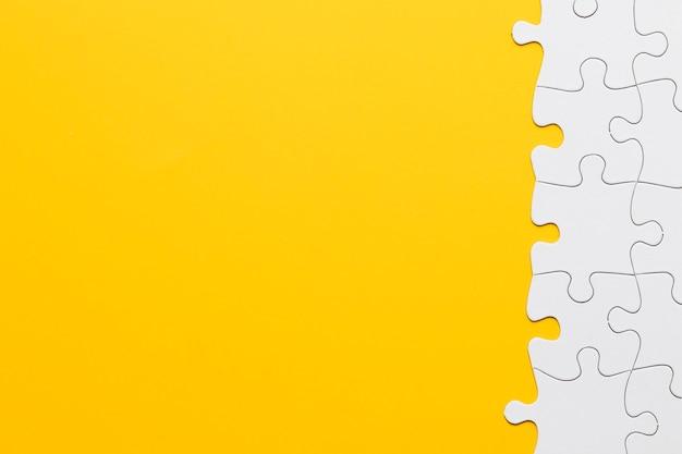 Verbundenes puzzlestück auf gelbem hintergrund