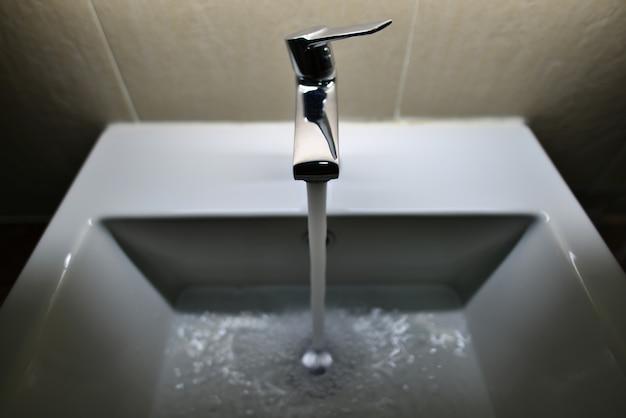 Verchromter wasserhahn mit fließendem wasser im badezimmer