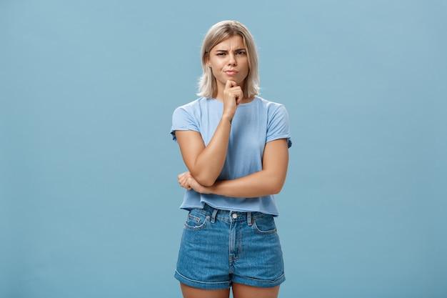 Verdächtige intensive kreative junge mitarbeiterin im outdoor-outfit, die von zweifelhaften gedanken, die hand am kinn halten, die stirn runzelt, während sie denkt, unglauben über blaue wand auszudrücken
