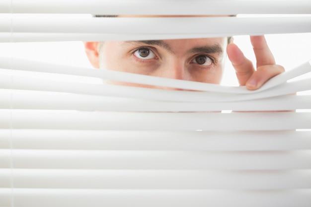 Verdächtige männliche augen, die durch rollo ausspionieren