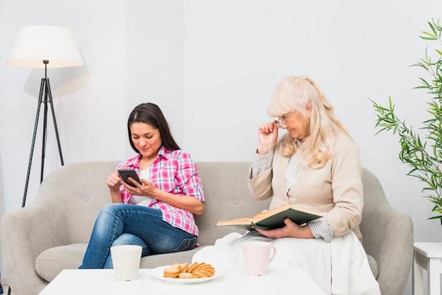 Verdächtige mutter, die ihre erwachsene tochter ausspioniert, die mitteilungen in einem smartphone schaut