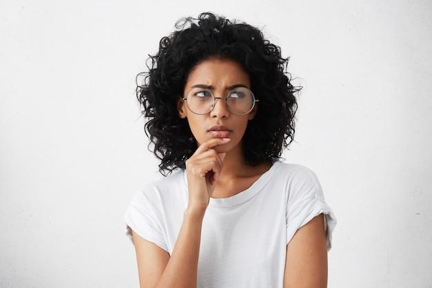 Verdächtige nachdenkliche junge mischlingsfrau mit schwarzen lockigen haaren, die nach oben schauen