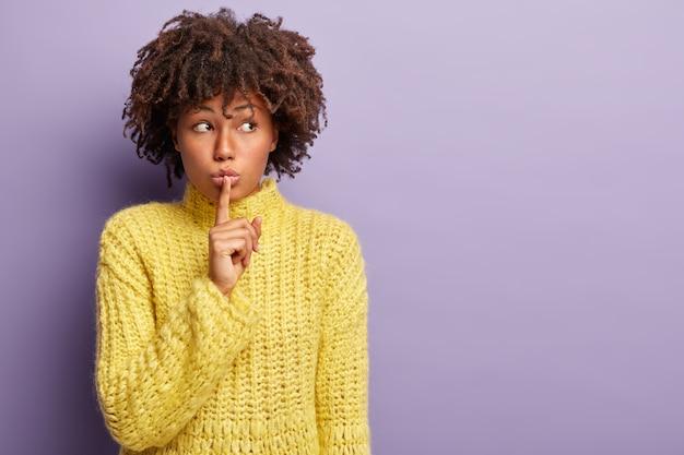 Verdächtige schöne frau bittet, mit dem finger auf den lippen ruhig zu sein, schaut zur seite, erzählt geheime informationen, konzentriert beiseite, bittet, den mund geschlossen zu halten, trägt gelbe kleidung, isoliert auf lila wand