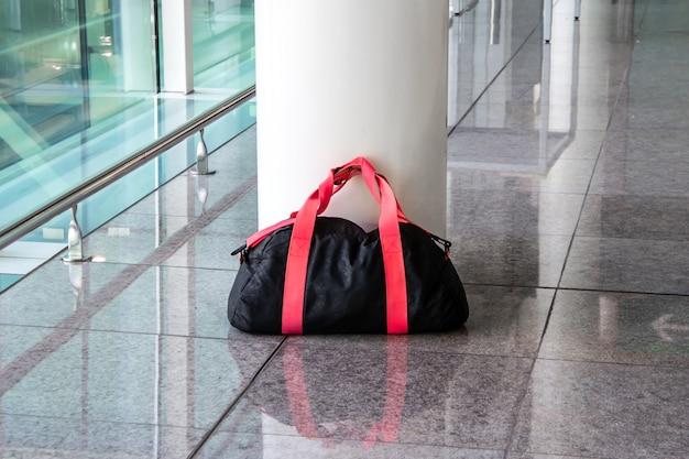 Verdächtige schwarz-rote tasche in einer leeren halle unbeaufsichtigt gelassen. konzept des terrorismus und der öffentlichen sicherheit. gefährliches inhaberloses verfallenes gepäck.